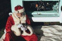 Человек в костюме Санта-Клауса пишет смс на мобильном телефоне, сидя в фургоне с открытым моторным отсеком — стоковое фото