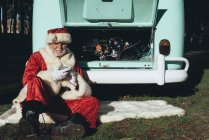 Man in costume of Santa Claus texting on mobile phone while sitting at van with open engine compartment — Stock Photo