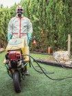 Spécialiste en uniforme pour fumigation tenant chariot jaune dans la cour — Photo de stock