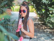 Smiling young female in sunglasses with dreadlocks drinking cocktail and looking at camera in park — Stock Photo