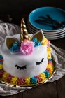 Cute unicorn cake with painted closed eyes on wooden table on dark background — Stock Photo