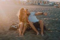 Молода пара в коханні вказуючи на море в романтичний вечір заходу сонця — стокове фото