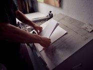 Руки безликого работника в процессе производства книги с использованием профессионального оборудования в типографии — стоковое фото