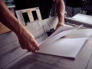Руки неузнаваемого сотрудника, использующего профессиональные инструменты для изготовления книг — стоковое фото