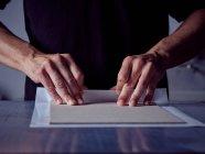 Ремесленные руки делают книгу жесткой, заворачивая картонный лист в белую бумагу — стоковое фото