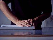 Руки сумасшедшего, делающего книгу в мастерской — стоковое фото