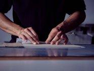 Руки переплётчика накладывая ткань на обложку для книги — стоковое фото