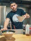 Молода людина в чорному футболку покласти на стіл чаші свіжої приготовленої японської блюдо називається рамен — стокове фото