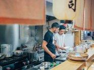Зверху кухня з молодими чоловіками готують японські страви рамен у східному ресторані — стокове фото