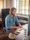 Man using computer in apartment interior — Stock Photo