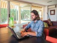 Обманутый мужчина работает с компьютером в квартире — стоковое фото