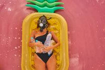 Overhead view of woman in respirator with plastic bottles lying on pineapple inflatable mattress in red water of tropical lagoon — Stock Photo