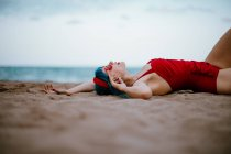 Fashionable woman with blue hairs in red bright swimsuit enjoying lying on sandy beach with stretched hands — Stock Photo