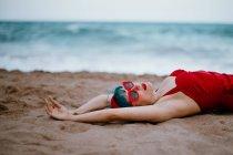 Модная женщина с голубыми волосами в красном ярком купальнике, наслаждающаяся лежащим на песчаном пляже с протянутыми руками — стоковое фото