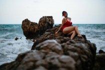 Femme à la mode avec des cheveux bleus en maillot de bain rouge brillant se reposant confortablement assis sur une pierre rocheuse sombre dans de l'eau de mer mousseuse — Photo de stock
