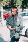 Femme d'affaires avec coiffure à la mode et costume tenant un ordinateur portable avec des jambes et regardant loin dans le parking au jour lumineux — Photo de stock