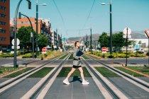 Vue latérale de la femme à la mode en costume élégant avec ordinateur portable noir rapide traversant la route, regardant autour — Photo de stock