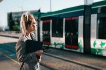 Сторона зору стильний модний бізнесмен чекає поїзд і пильно дивлячись геть на станції — стокове фото