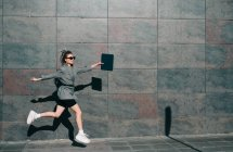 Side view of stylish businesswoman jumping along marble wall and waving hands with tablet — Stock Photo