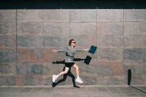 Vue latérale d'une femme d'affaires élégante sautant le long d'un mur de marbre et agitant ses mains avec une tablette — Photo de stock