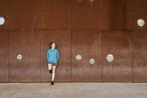 Jogger taking break and leaning against wall — Stock Photo