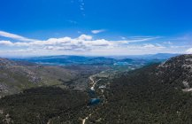 Vista aerea di un bellissimo paesaggio, cielo blu nuvoloso e laghi circondati da boschi e montagne — Foto stock