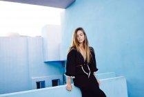 Mulher bonita apoiando-se no moderno edifício de parede azul e olhando para baixo — Fotografia de Stock