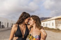 Affectionate female couple walking by old town, embracing and touching with foreheads — Stock Photo