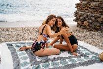 Вид сбоку стильных молодых женщин в купальниках, расслабляющихся на берегу моря и фотографирующихся на смартфон — стоковое фото