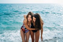 Cheerful young lesbian women in swimsuits embracing on beach by water on sunny day — Stock Photo