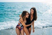 Fröhliche junge lesbische Frauen in Badeanzügen, die sich an sonnigen Tagen am Strand am Wasser umarmen — Stockfoto