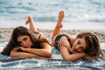 Happy young women in swimwear relaxing on blanket with raised feet — Stock Photo
