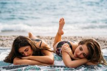 Happy young women in swimwear relaxing on blanket on seashore — Stock Photo