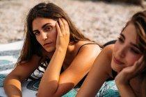 Щасливі молоді жінки в купальнику відпочивають на укритті на пляжі. — стокове фото