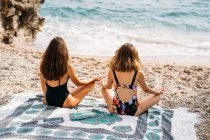 Back view of women in swimsuits sitting on blanket in lotus position while practicing yoga by stone construction — Stock Photo