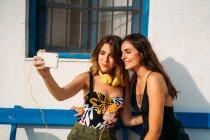 Jovens felizes em tops e shorts sentados no banco, abraçando e tirando selfie no smartphone — Fotografia de Stock