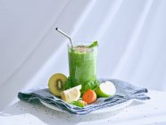 Set of ingredients for healthy smoothie and glass with green drink — Stock Photo