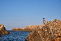 Child standing on cliff on seashore — Stock Photo