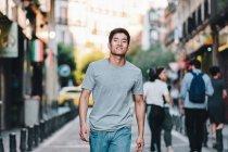 Contenidos asiáticas camisas vestidas paseando por la calle de verano urbana - foto de stock