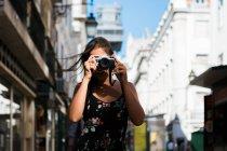 Уверенная женщина в летнем платье фотографируется с камерой, стоя на живописной солнечной улице города — стоковое фото