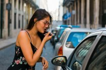 Side view of carefree woman in sunglasses and dress putting on bright lipstick while looking at car window — Stock Photo