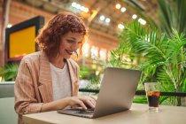 Счастливая молодая деловая женщина сидит за столом с холодным напитком в кафе и использует ноутбук для работы — стоковое фото