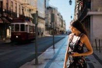 Belle femme confiante en robe d'été tenant un appareil photo debout sur la rue ensoleillée pittoresque de Lisbonne, Portugal — Photo de stock