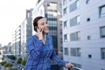 Красивая деловая женщина в синей клетчатой рубашке хмурясь и глядя в сторону, стоя на балконе — стоковое фото