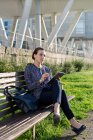 Serious female entrepreneur in elegant jacket frowning and using tablet while sitting on bench on sunny day in city park — Stock Photo
