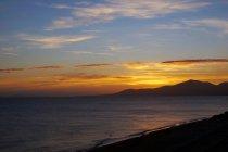 Coucher de soleil éclatant au-dessus d'un paysage mystérieux d'eau ondulée qui lave le rivage rocheux à Lanzarote, îles Canaries, Espagne — Photo de stock