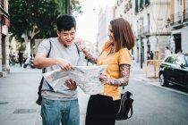 Positivo ridere persone multietniche in cerca di direzione sulla mappa mentre in piedi sulla strada della città — Foto stock