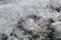 Melting ice and snow on top of rocky surface with pebbles in daylight — Stock Photo