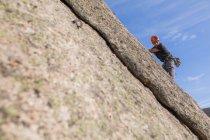 Da sotto l'uomo scalare una roccia in natura con attrezzatura da arrampicata — Foto stock