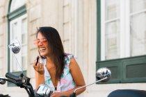 Insouciante belle femme en lunettes de soleil portant rouge à lèvres lumineux tout en regardant miroir moto sur la rue — Photo de stock